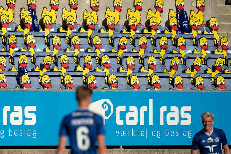 1. Juni, Kopenhagen: Zwei Spieler des Lyngby BK stehen während ihres Spiels gegen den FC Kopenhagen vor leeren Zuschauertribünen, die durch Abbilder von Enten besetzt wurden. Erst Mitte Juni wurden mehr als 500 Zuschauer erlaubt. Das Pokalfinale bildete eine Ausnahme.