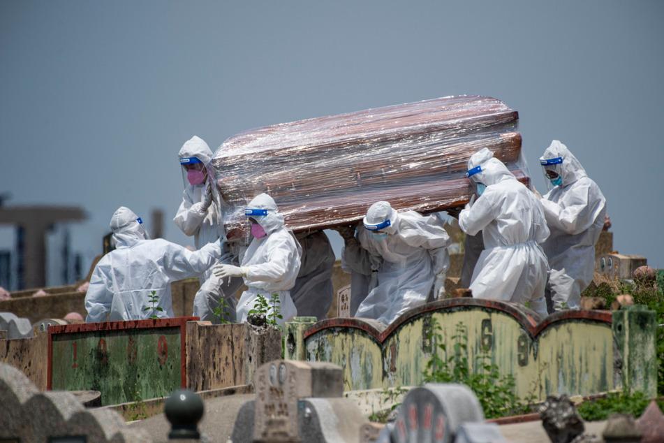 Malaysia, Selangor: Menschen in Schutzanzügen tragen den Sarg eines Corona-Opfers auf einen Friedhof.