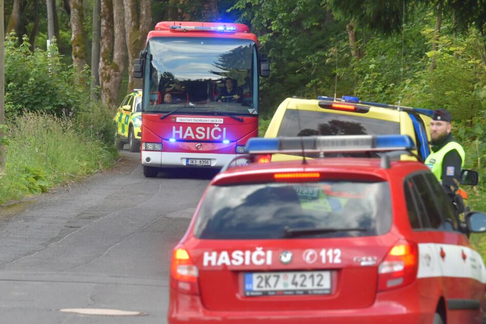 Ein Bus der Feuerwehr sowie Rettungskräfte stehen in der Nähe eines Zugunglücks an einer Straße.