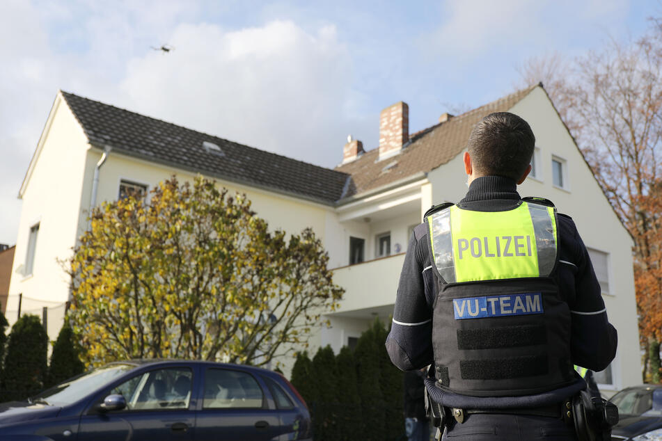 Ein Polizist steuert zur Spurensicherung eine Drohne über einem Grundstück.