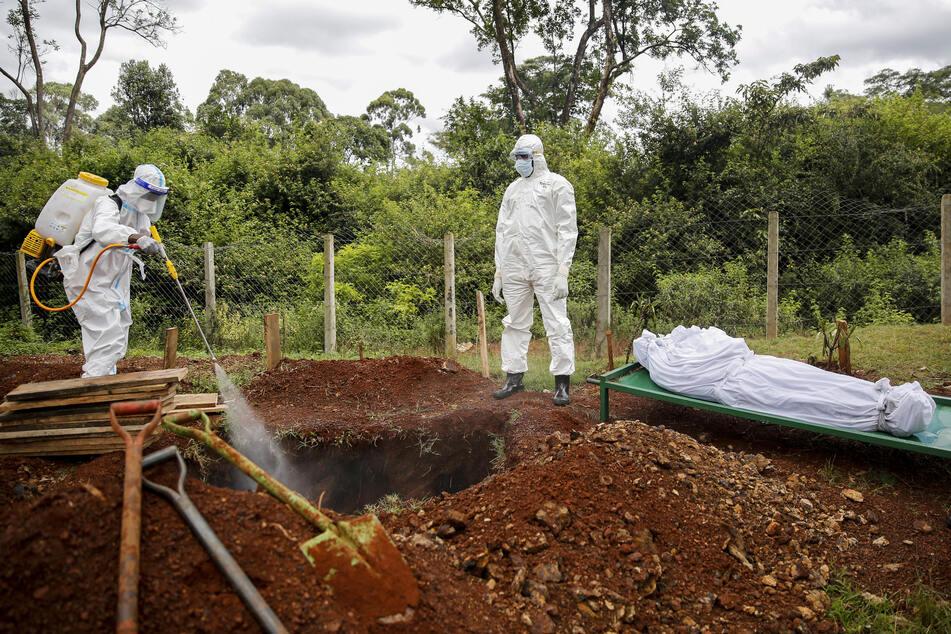 Kenia, Nairobi: Ein Mitglied in Schutzanzug eines Teams, das für die Beerdigungen von muslimischen Corona-Toten zuständig ist, sprüht Desinfektionsmittel auf die Leiche eines Mannes auf dem muslimischen Friedhof Langata.