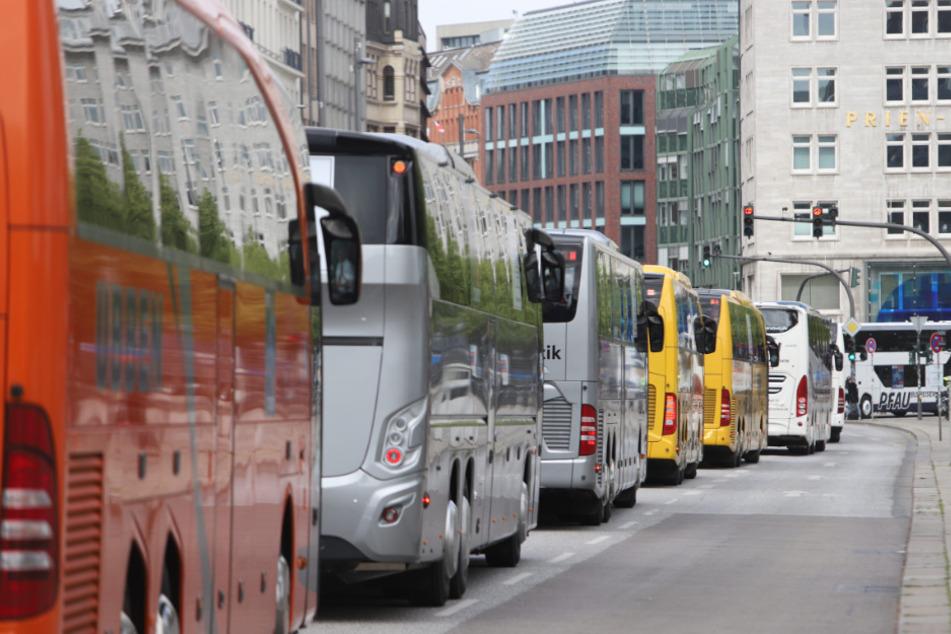 Reisebusse reihen sich auf einer Straße, die zur Alster führt.