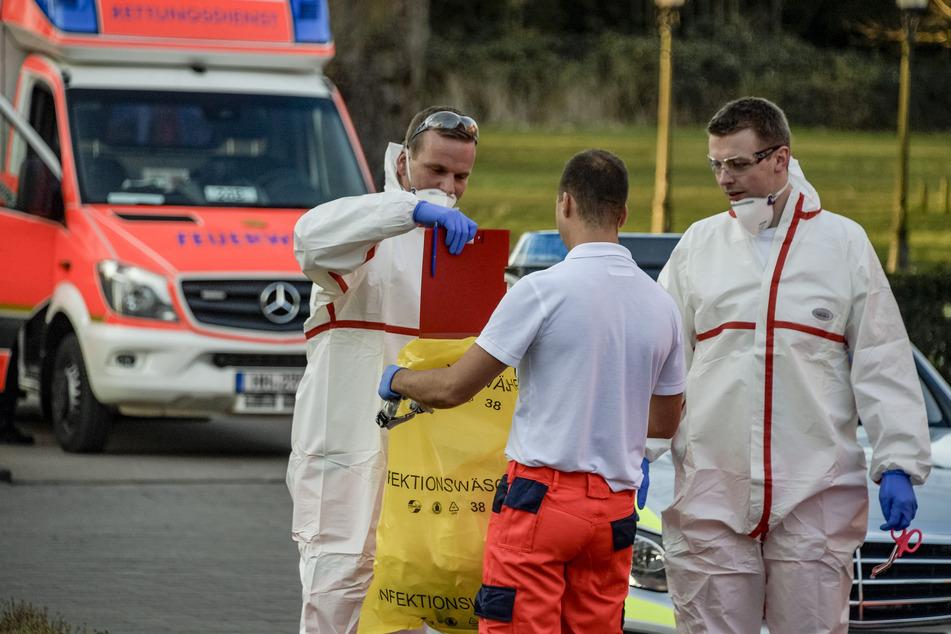 Rettungssanitäter der Feuerwehr packen vor einem Altenheim, in dem mehrere Bewohner positiv auf Covid-19 getestet worden sind, Arbeitsmittel und Schutzanzüge in einen Plastiksack.