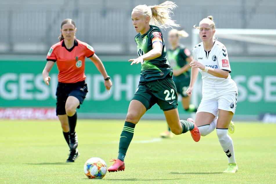 Pernille Harder (m.) vom VfL Wolfsburg wird von Freiburgs Janina Minge (r.) verfolgt.