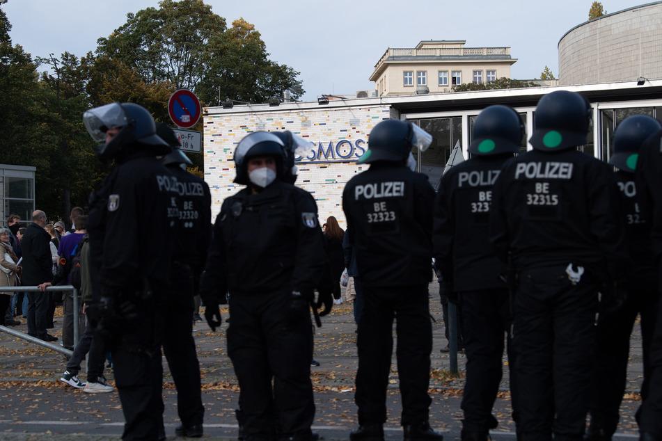Teilnehmer der Demonstration gegen die Corona-Auflagen stehen vor dem Kosmos. Polizisten beobachten das Geschehen.