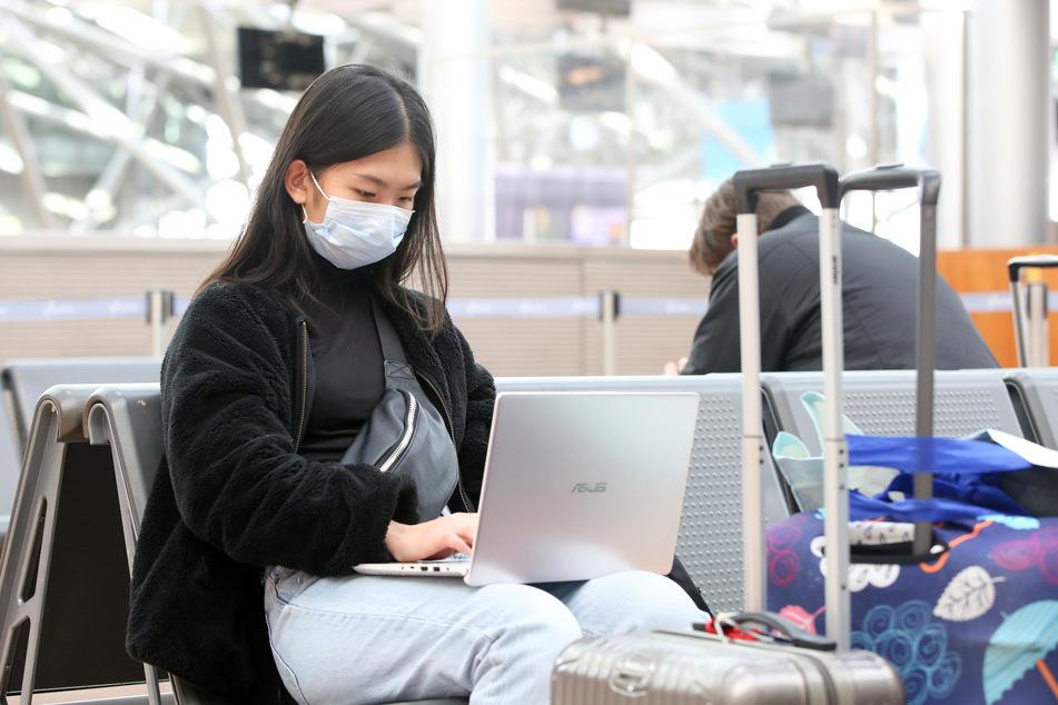 Ein junge Frau aus Indonesien sitzt mit einem Mundschutz in einer Abfertigungshalle im Flughafen Hamburg.
