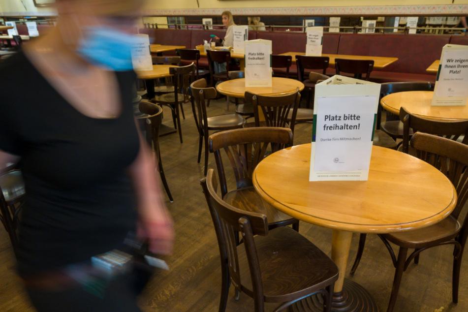 Schilder, die zum Abstandhalten, die Zuweisung zu den Plätzen und anderer Verhaltensregeln hinweisen, stehen auf den Tischen des Restaurants Voila im Münchner Stadtteil Haidhausen.
