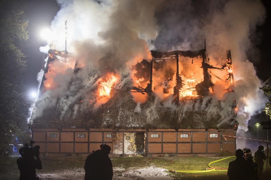 Feuerwehrleute löschen die brennende Scheune.