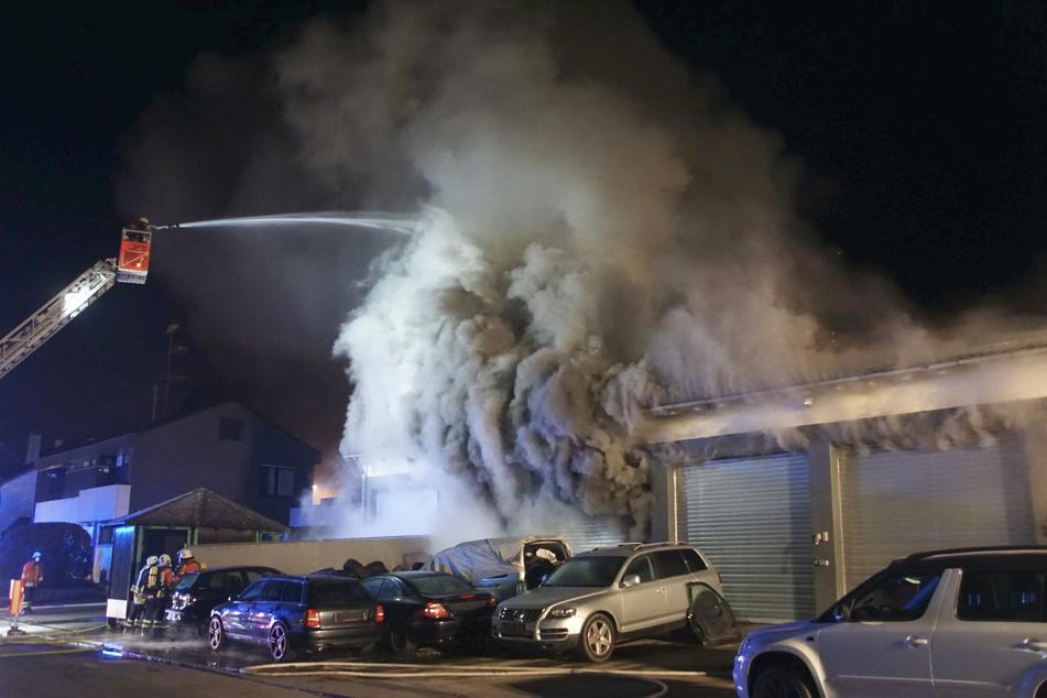 Feuerwehrleute löschen den Brand in der Autowerkstatt.