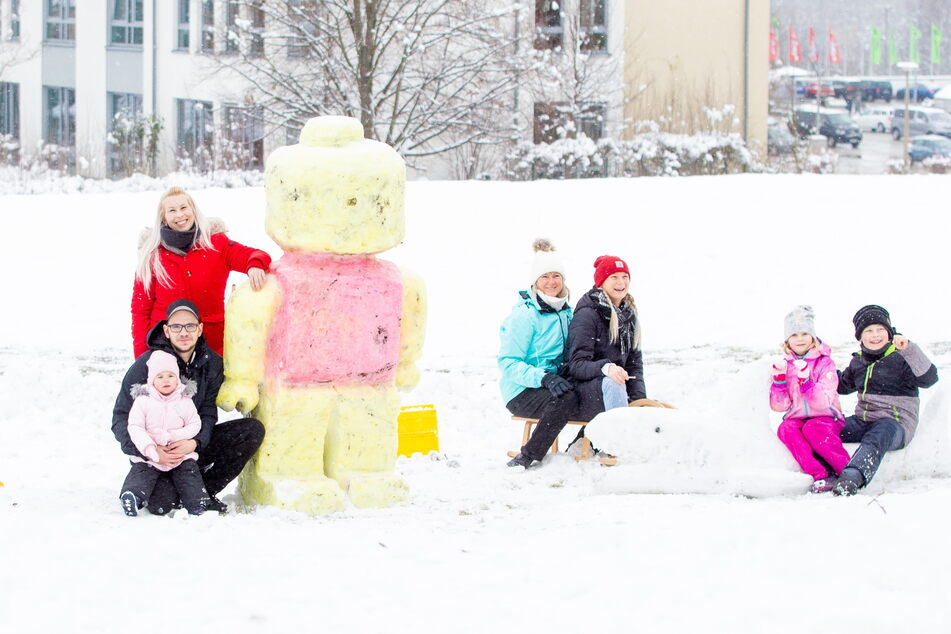 Benjamin Völker und Sandy Rosenberg (ganz links) haben eine Lego-Figur aus Schnee für ihre Kinder Amberly und John (ganz rechts) kreiert.