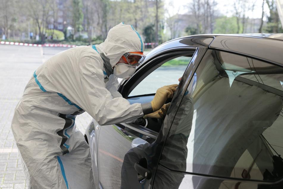 Ein Mitarbeiter der Stadt Düsseldorf nimmt an der Corona Teststelle auf dem Parkplatz der Mitsubishi Electric Halle einen Abstrich vor.