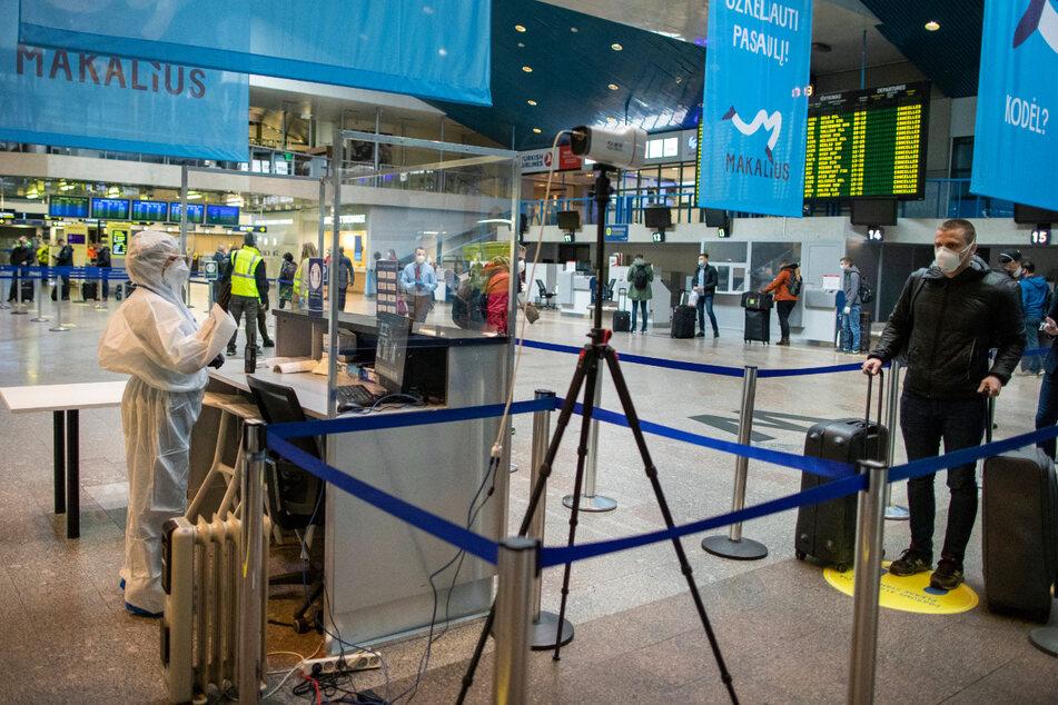 Ein Flughafenmitarbeiter kontrolliert die Temperatur der Passagiere auf dem Internationalen Flughafen Vilnius.