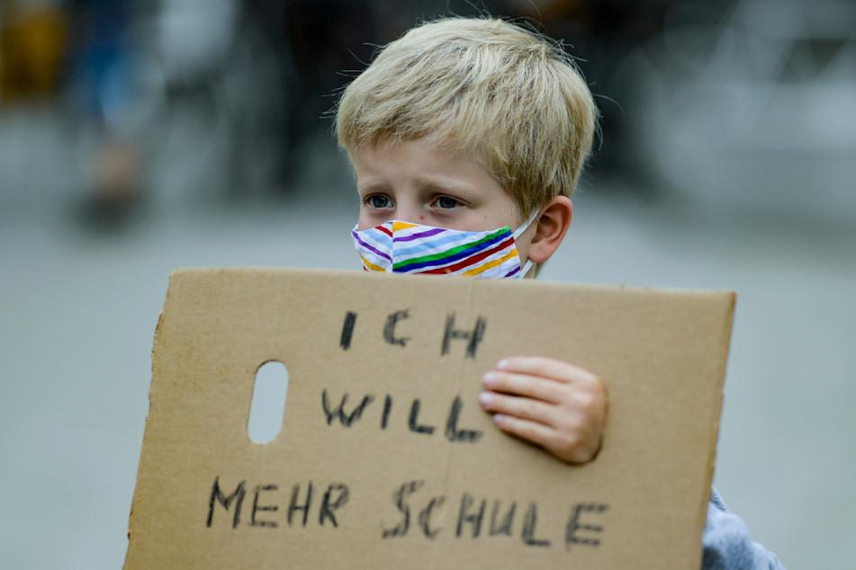 """Ein Junge trägt einen bunt gestreiften Mund-Nasenschutz, während er ein Stück Pappkarton mit der Aufschrift """"Ich will mehr Schule"""" auf dem Gänsemarkt in Hamburg vor sich hält."""