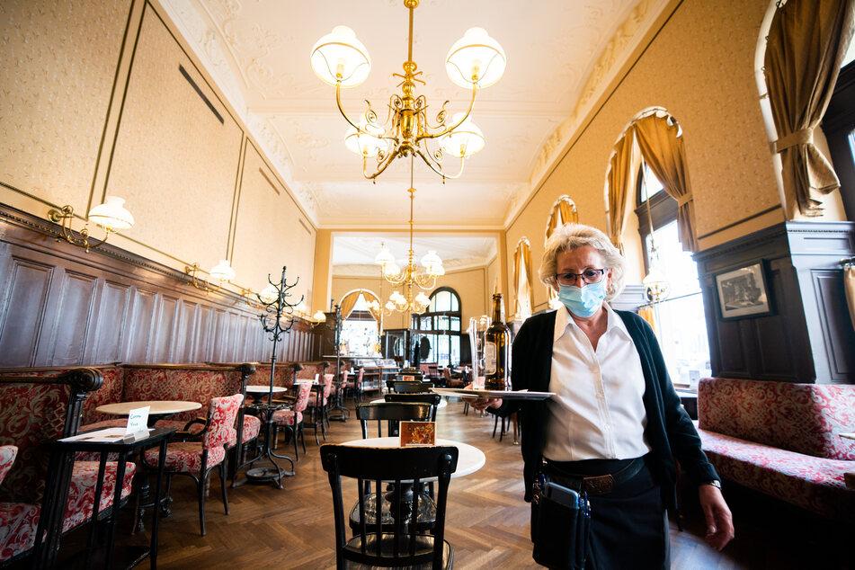 Eine Kellnerin mit Mund- und Nasenschutz wartet im Cafe Sperl in Wien auf Gäste.