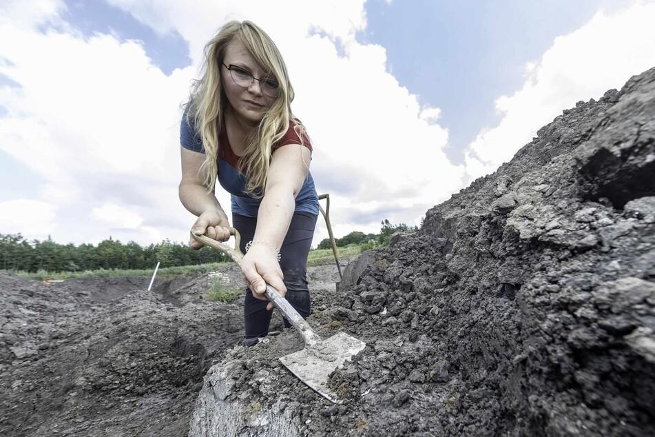 Svenja Warnke, ehrenamtliches Mitglied des Grabungsteams, demonstriert, wie das Team durch das Abtragen dünner Tonschichten nach den Knochen der Ur-Meeresbewohner sucht.