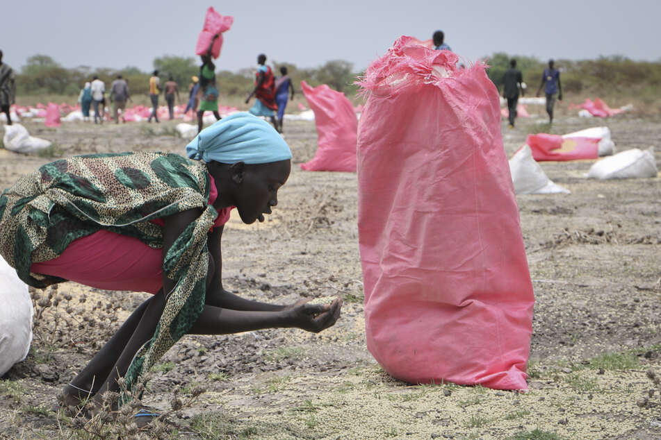 Südsudan, Kandak: Eine Frau sammelt Hirse vom Boden auf, die in Säcken vom Welternährungsprogramm (WFP) der Vereinten Nationen über der Stadt abgeworfen wurden.