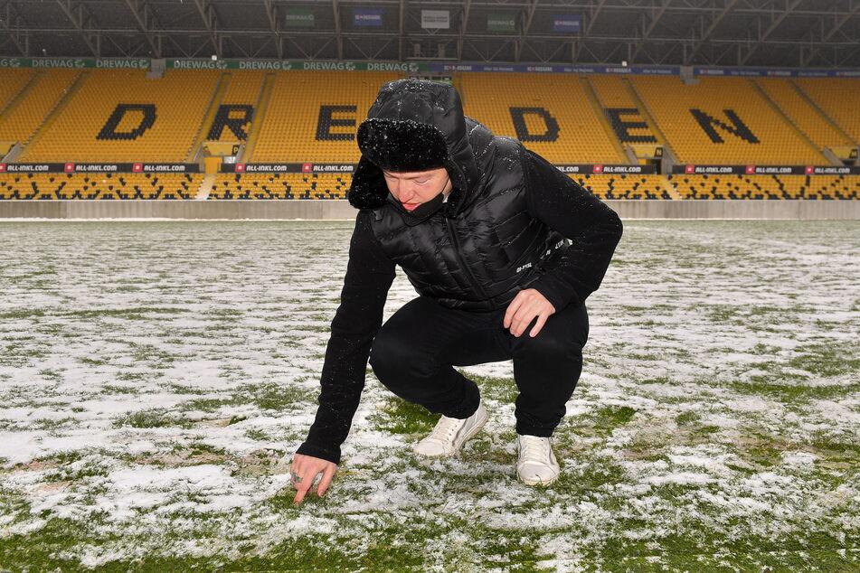 Ronald Tscherning, Leiter der Stadion Dresden Projektgesellschaft, zeigt auf dem Rasen die Beschaffenheit des Schnees.