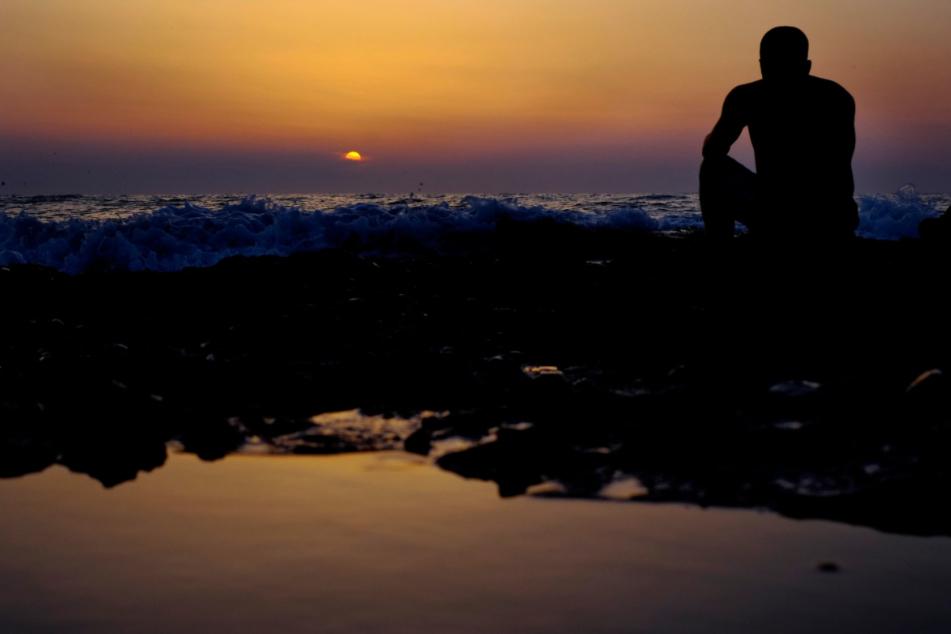 Zypern, Ayia Eirini: Ein Mann sitzt bei Sonnenuntergang auf einem Felsen am Meer.
