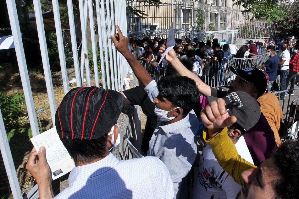 Migranten stehen vor einem Zaun rund um den Zentralen Asyldienst, um Informationen über ihre Aufenthaltsgenehmigungen zu erhalten.