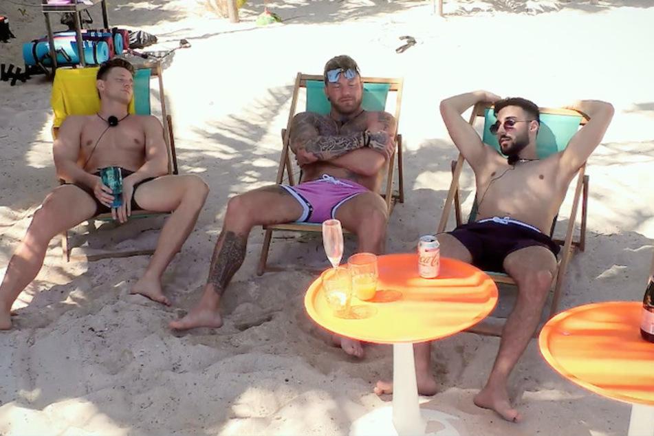Tommy (25, v.l.), Till (32) und Halil (22) unterhalten sich am Strand in Mexiko über ihre Optionen bei den weiblichen Teilnehmerinnen.