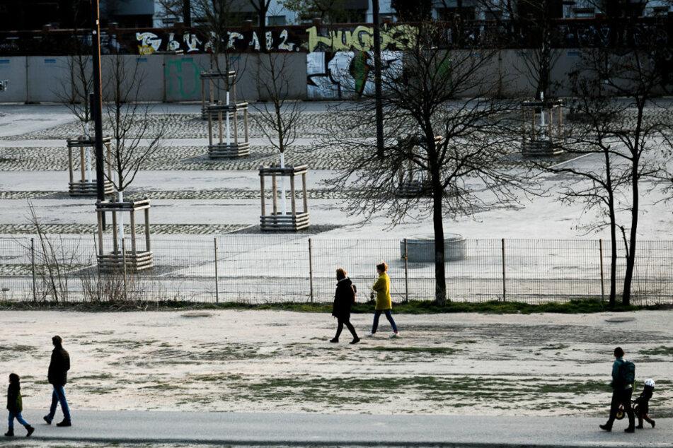 Menschen gehen im Mauerpark mit großem Abstand zueinander spazieren.