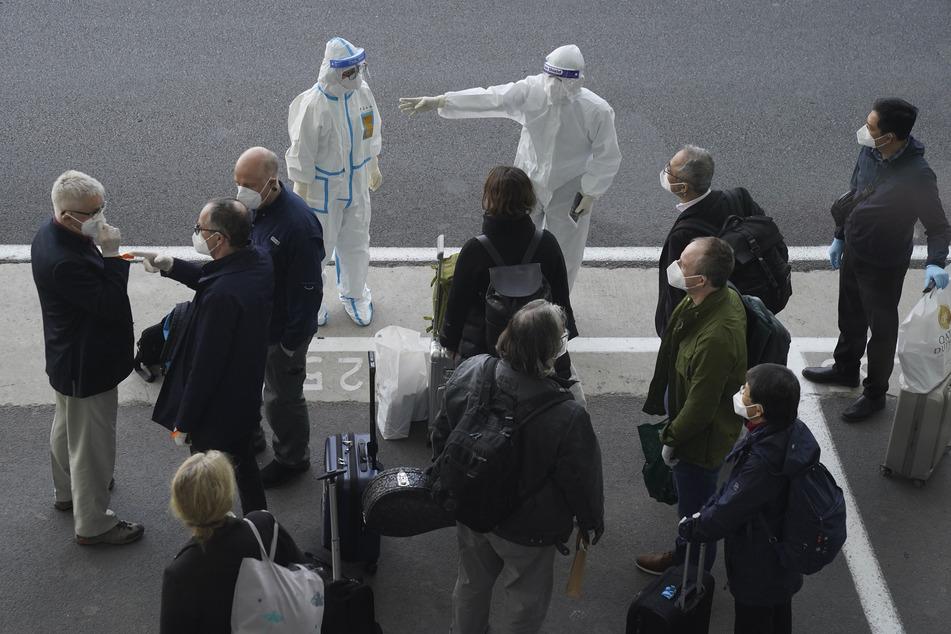 Arbeiter in Schutzkleidung sprechen mit Mitgliedern eines Teams der Weltgesundheitsorganisation (WHO) am Flughafen in Wuhan.