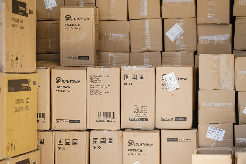Kartons voll mit Masken lagern in einem Container.