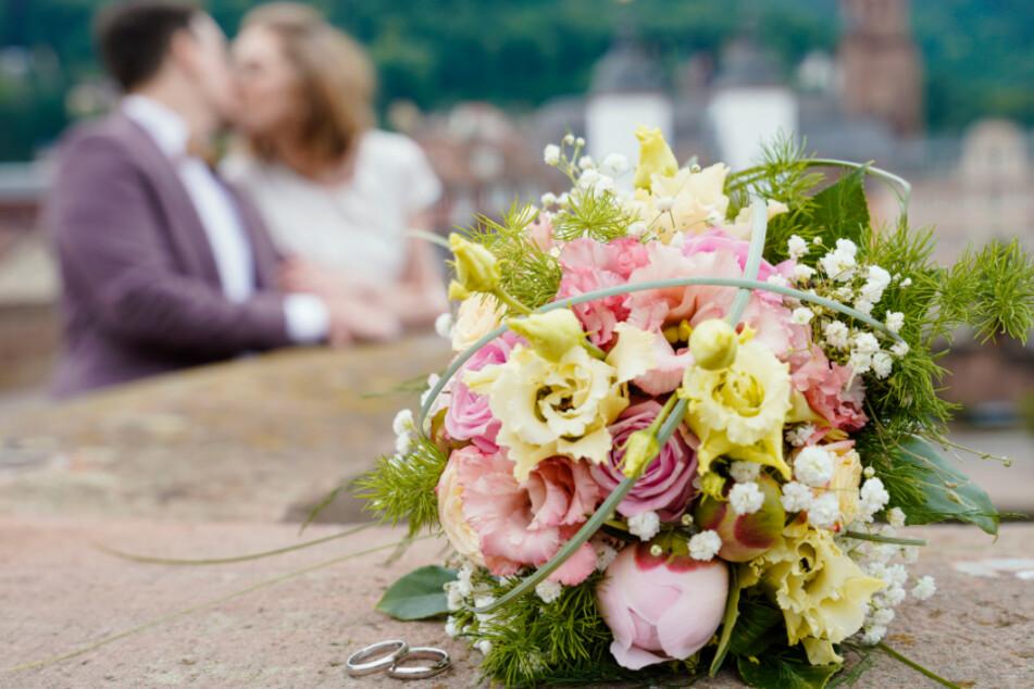 Ein frisch vermähltes Brautpaar küsst sich auf der Alten Brücke hinter ihrem Blumenstrauß und den beiden Eheringen, die auf dem Brückengeländer liegen.