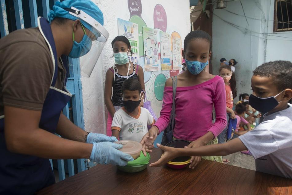 Kinder aus dem Stadtviertel Petare erhalten ein Lunchpaket aus einer Suppenküche.