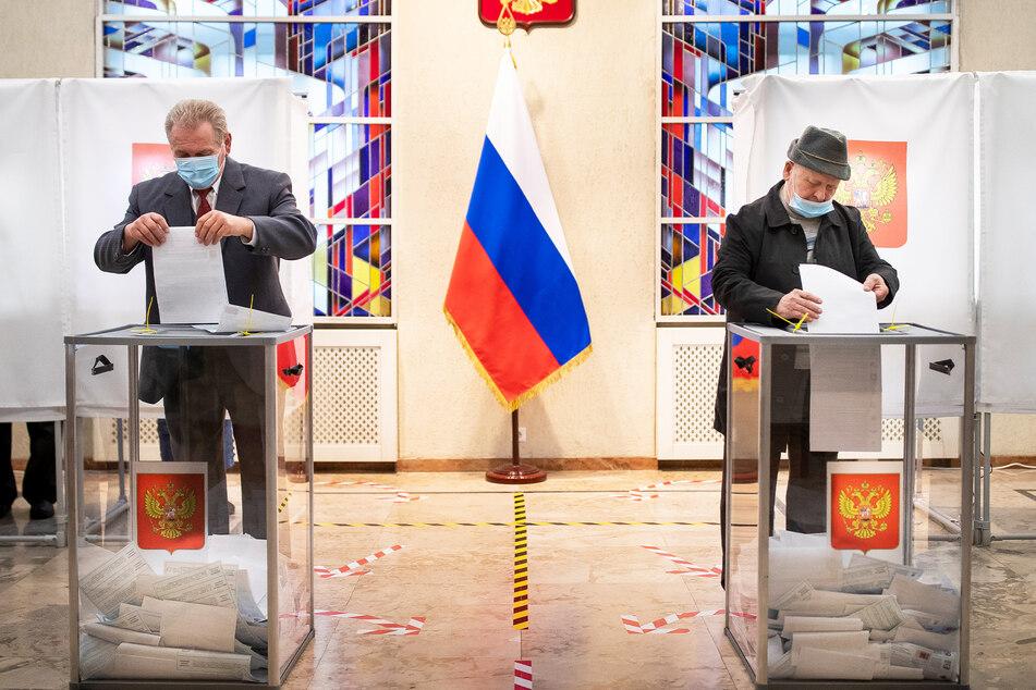 Zwei Russen werfen ihre Stimmzettel in die Wahlurnen in der russsischen Botschaft in Litauen.