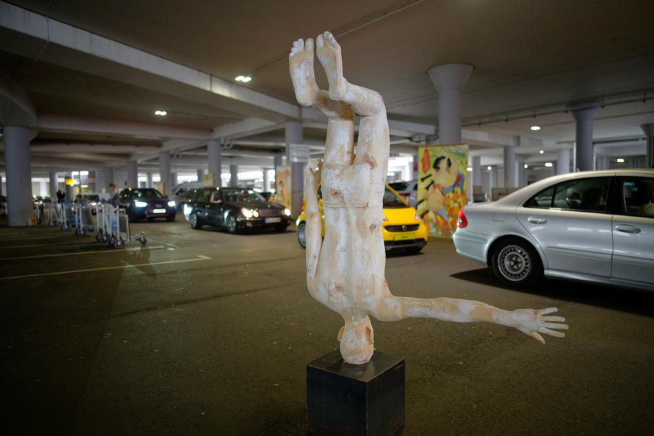 Ausstellungsbesucher fahren in Autos an der Skulptur des Künstlers Hubert Mussner vorbei, welche im Parkhaus P1 des Flughafens Köln-Bonn steht.