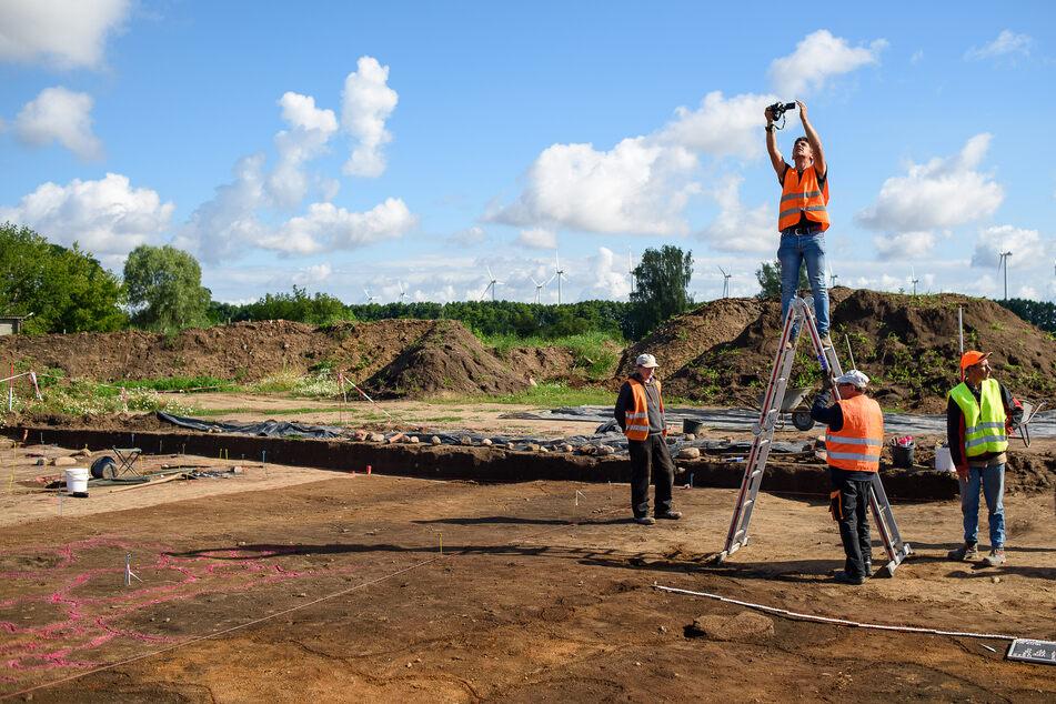 Archäologen vom Landesamt für Denkmalpflege und Archäologie Sachsen-Anhalt fotografieren die Grabungsfläche.