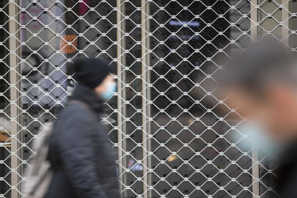 Menschen mit Mundschutz gehe an einem geschlossenen Geschäft in der Stuttgarter Königsstraße vorbei.