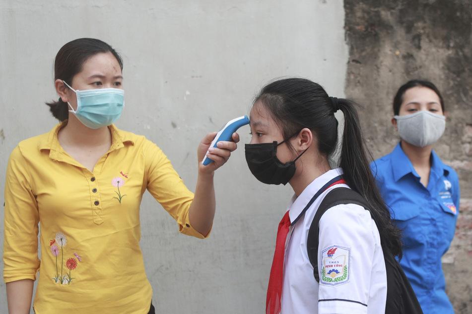 Bei einer Schülerin wird mithilfe eines Thermometers ein mögliches Fieber gemessen, bevor sie in die Dinh-Cong-Mittelschule in der vietnamesischen Hauptstadt Hanoi geht. (Archivbild)