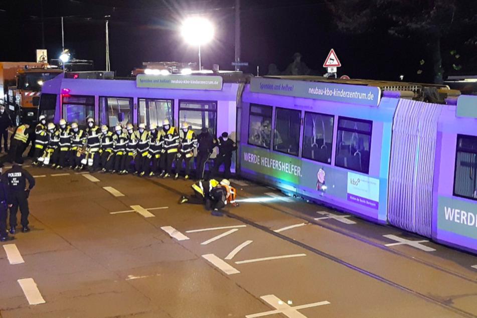 Einsatzkräfte der Feuerwehr schieben die Tram mit vereinten Kräften zurück auf die Schienen.