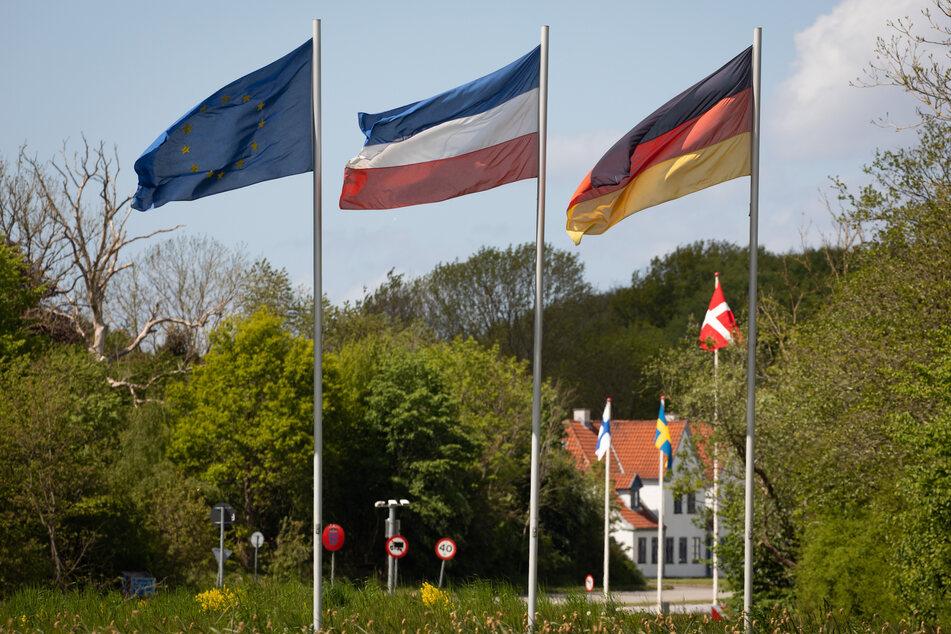 Die Flaggen von Europa (l-r), Schleswig-Holstein, Dänemark und Deutschland wehen am deutsch-dänischen Grenzübergang Kupfermühle/Krusa bei Flensburg.