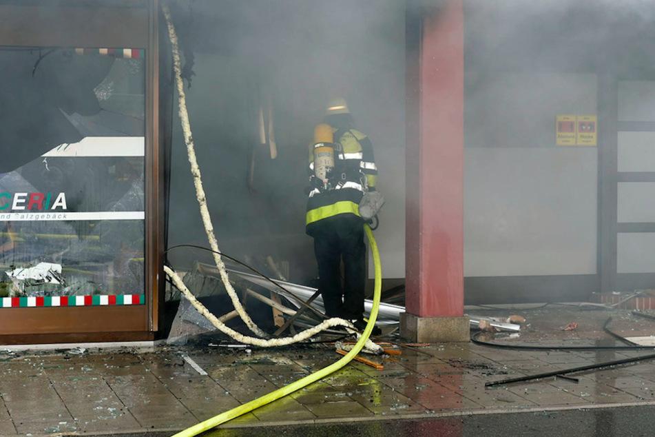Ein Feuerwehrmann löscht den Brand in der Pizzeria.