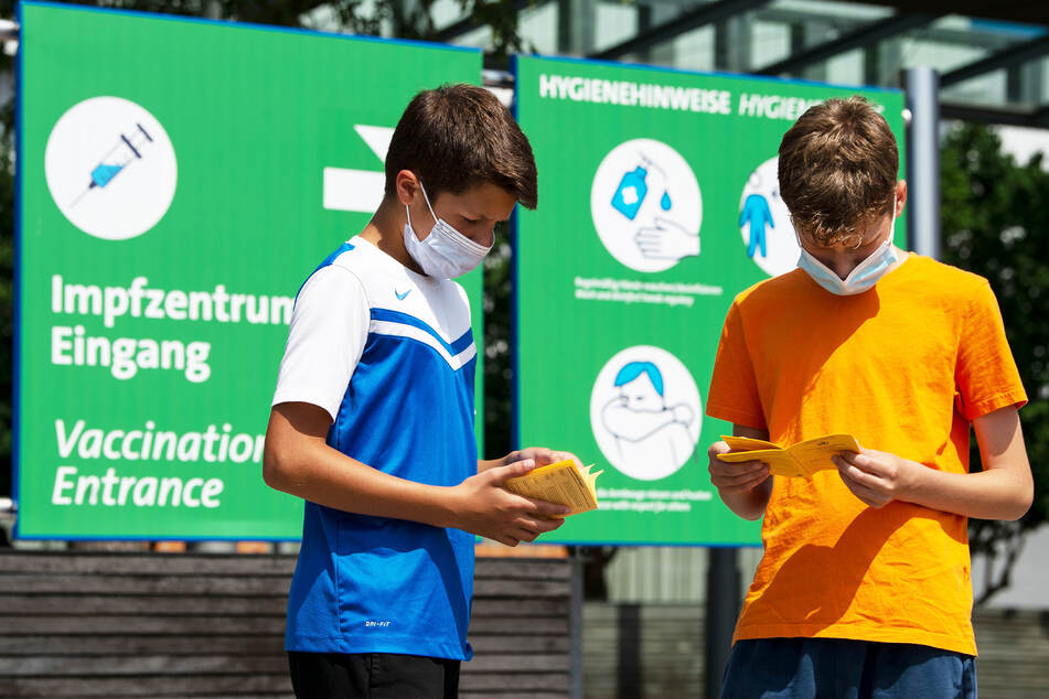Die Geschwister Hugo (12) und Urs (13) blättern vor einem Impfzentrum in ihren Impfbüchern. In Sachsen dürfen sie sich nun gegen Corona immunisieren lassen.