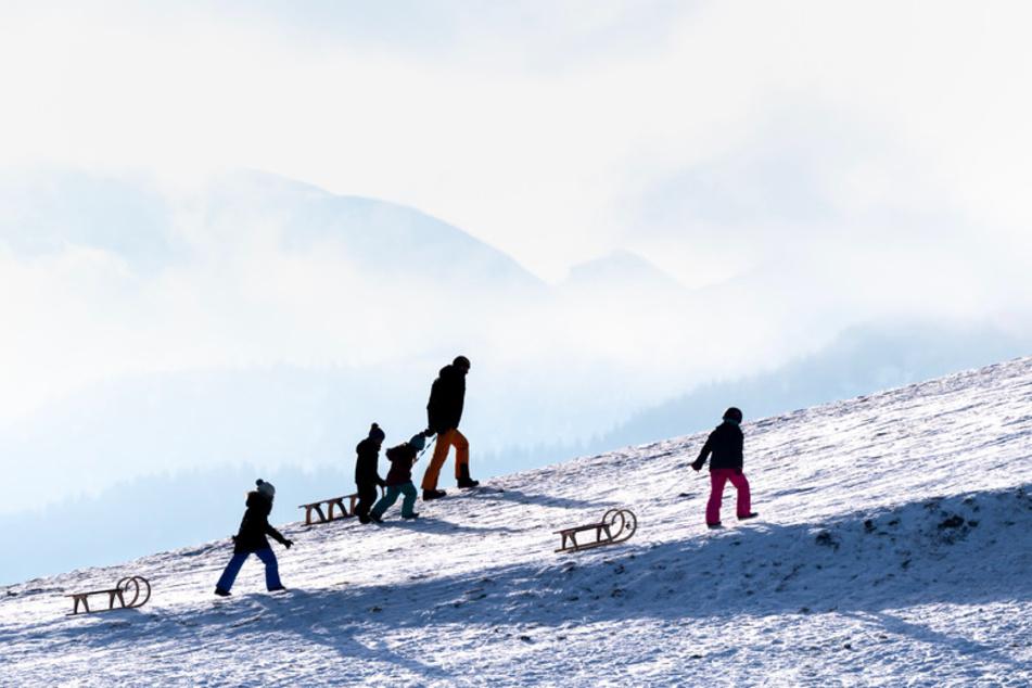 Ein Mann und drei Kinder ziehen Schlitten einen verschneiten Hang bei Hundham hinauf, während im Hintergrund die wolken- und nebelverhangenen Berge zu sehen sind.
