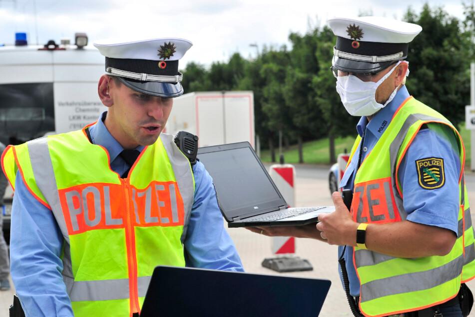 Elektronisches Lagezentrum auf der Motorhaube: Polizeioberkommissar Gunar Schreiber (31, l.) beobachtet die Live-Bilder aus dem Hubschrauber.