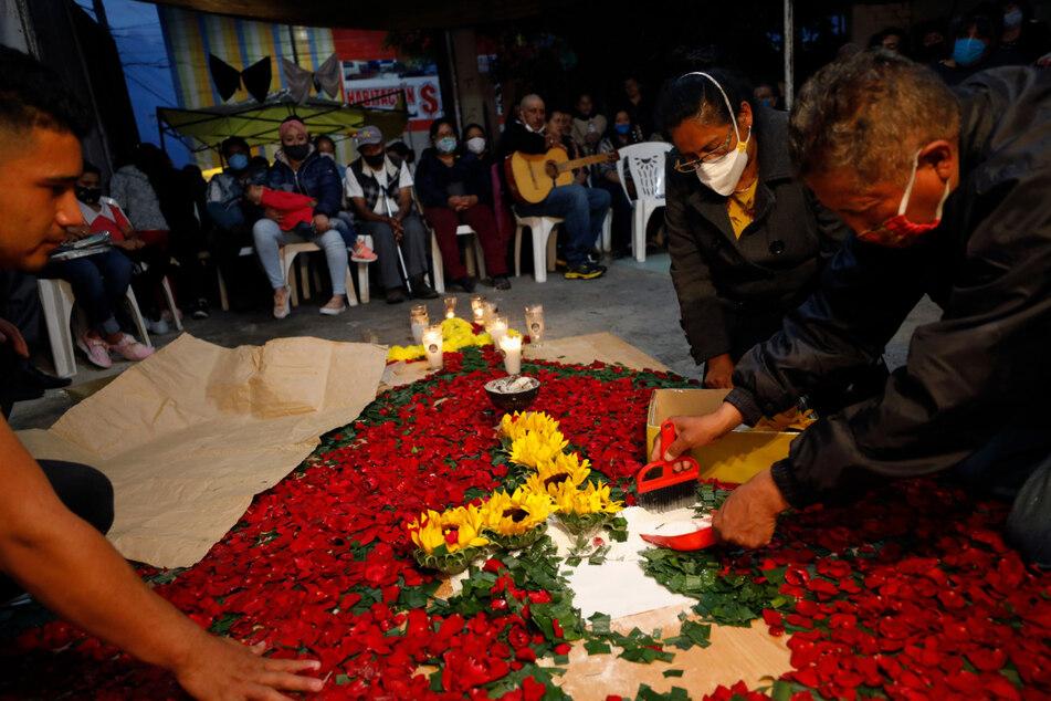 Im mexikanischen Valle De Chalco sammeln Familienmitglieder Blumen für das Grab einer Angehörigen.