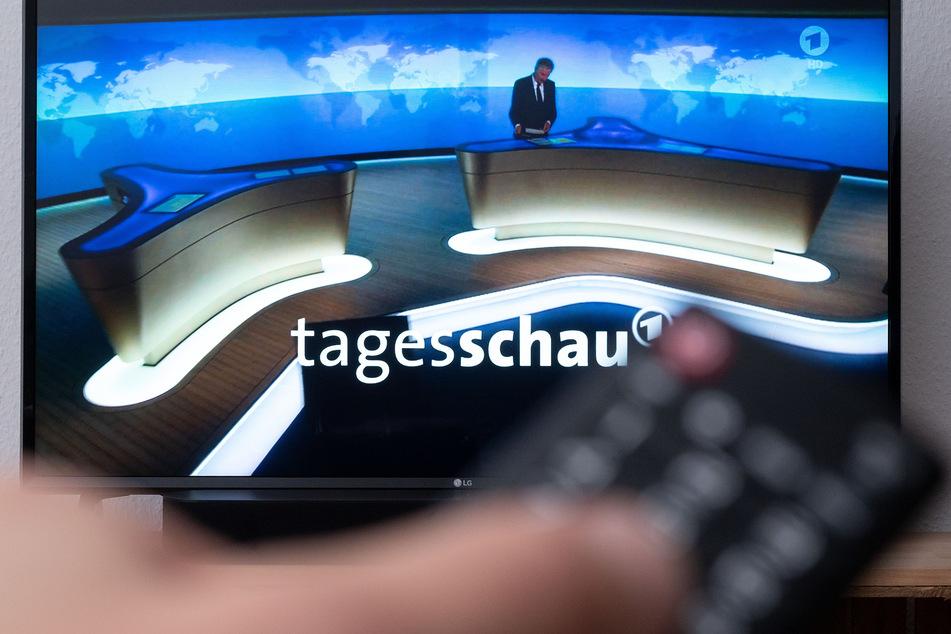 Ein Mann hält eine Fernbedienung vor einen Fernseher, auf dem die Tagesschau läuft.
