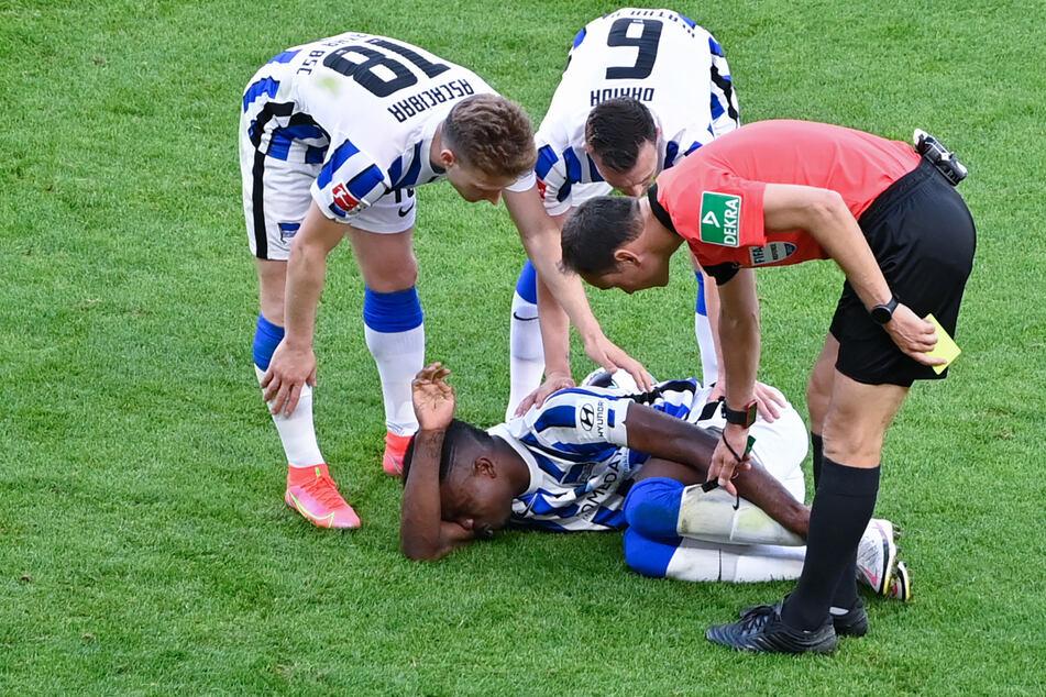 Herthas Santiago Ascacbiar (l.) und Vladimir Darida (M) kümmern sich um den verletzten Jhon Cordoba (am Boden). Der Kolumbianer fällt für den Rest der Saison aus.