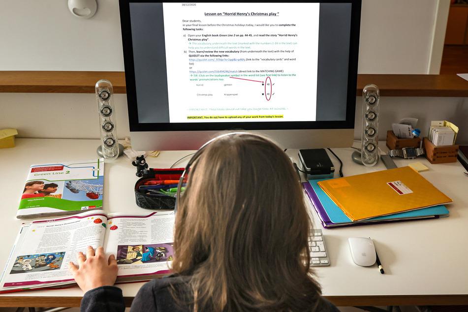 Ein zwölfjähriger Gymnasiast löst am Computer in seinem Zuhause seine Schulaufgaben, die ihm seine Lehrer über den Schulserver geschickt haben.