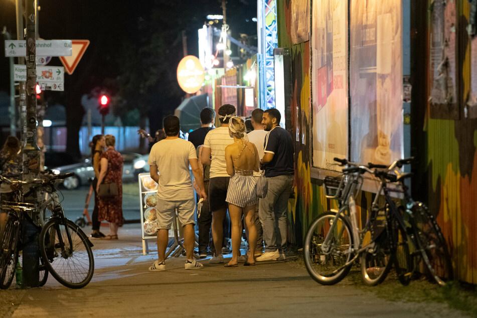 Partygänger stehen in den Abendstunden vor einem Club und warten auf Einlass. Nach den Corona-Lockerungen dürfen die Clubs wieder öffnen.
