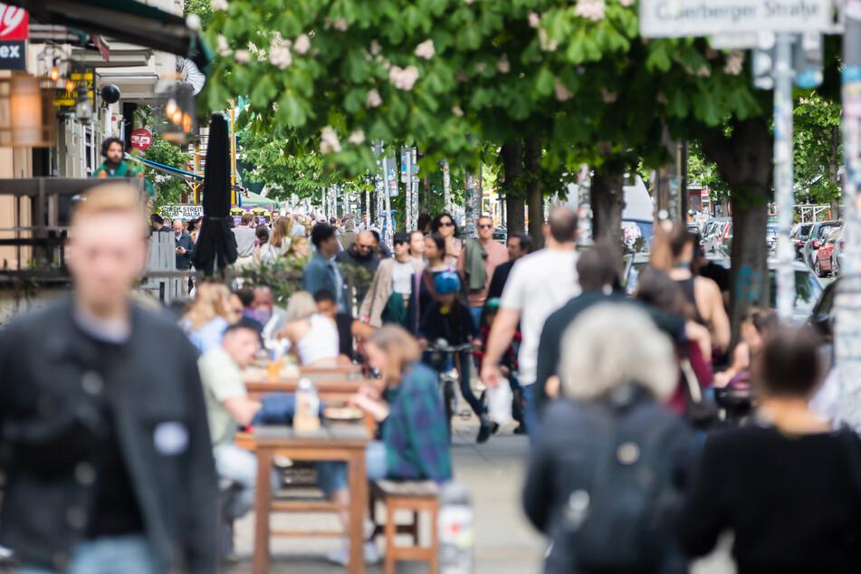 Passanten gehen im Berliner Bezirk Prenzlauer Berg an einem Restaurant vorbei.