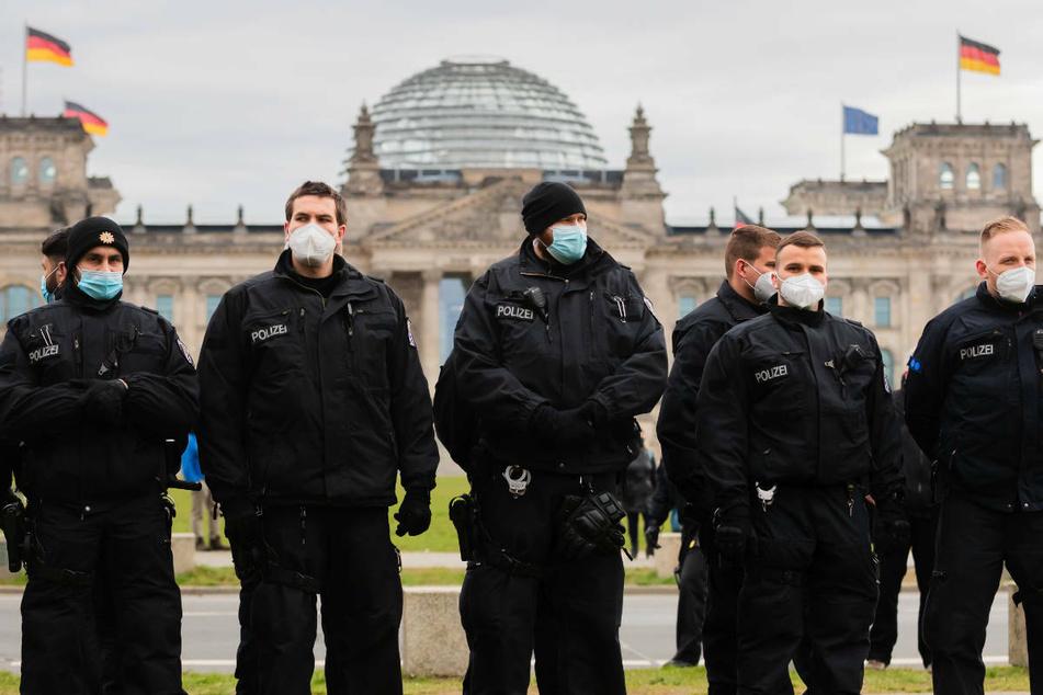 Polizisten stehen bei einer Kundgebung gegen die Corona-Maßnahmen vor dem Reichstagsgebäude. Auch am Mittwoch sind in Berlin mehrere Demonstrationen wegen der Abstimmung über das geänderte Infektionsschutzgesetz geplant.