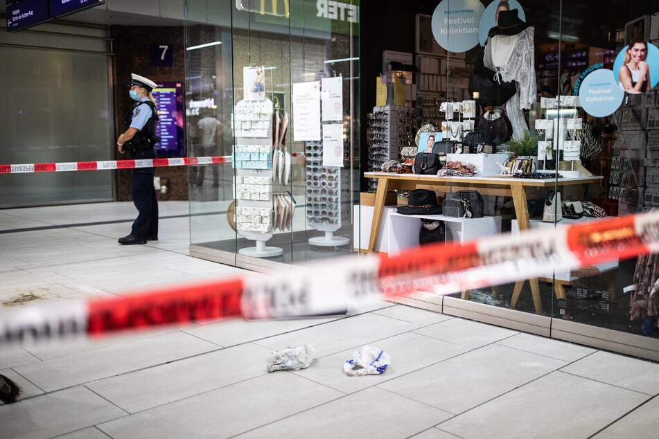 Einsatzkräfte der Polizei stehen im Hauptbahnhof vor einem Ladenlokal mit eingeschlagener Scheibe und Brandspuren auf dem Boden.