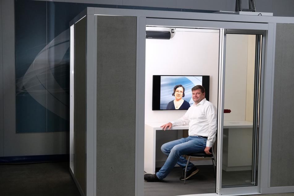 """Jan Wabst, Geschäftsführer der Seiwo Technik GmbH, sitzt in seinem Betrieb bei einer Präsentation in einem flexiblen Corona-Schutzraum, dem """"Protect Cube"""". Das Gerät desinfiziert sich automatisch mit UVC-Licht."""