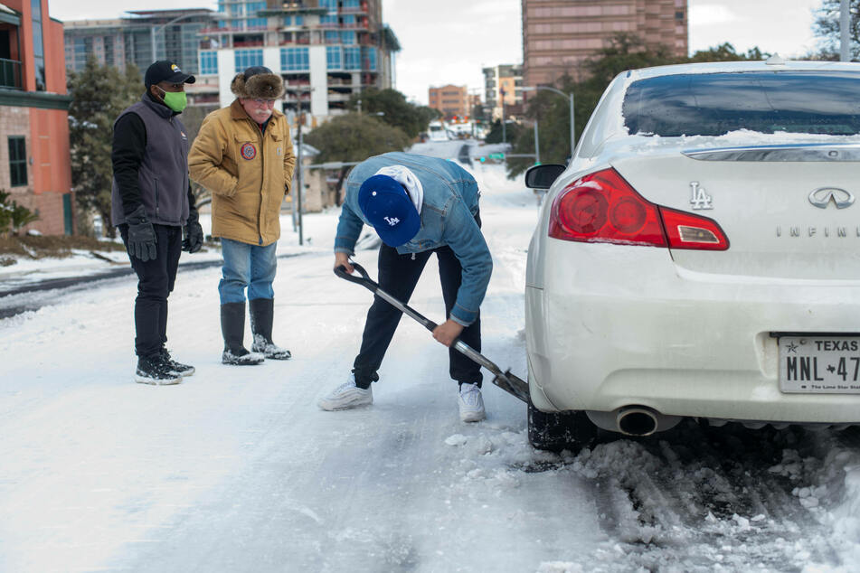 Austin, Texas: a man shovels ice from underneath his car tires after getting stuck in thick snow.